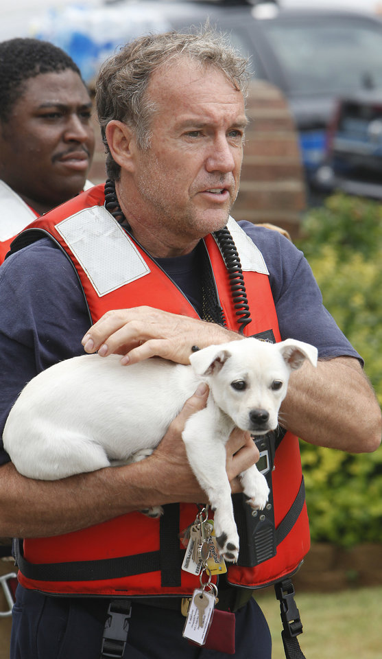 Oklahoma City Fire Fighter Allen Hill carry Lexie a mixed breed dog he rescued from a flooded house in The Valley in Edmond, Monday,  June 14, 2010. Photo by David McDaniel, The Oklahoman