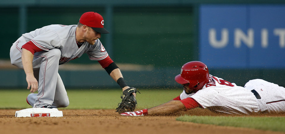 Photo - Washington Nationals' Anthony Rendon (6) is out a second base on the tag by Cincinnati Reds shortstop Zack Cozart (2), as he tries to stretch a single into a double during the third inning of a baseball game at Nationals Park Monday, May 19, 2014, in Washington. (AP Photo/Alex Brandon)