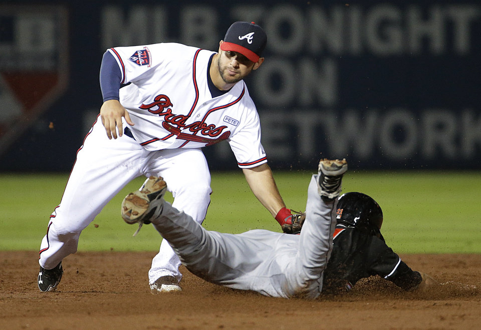 Photo - Miami Marlins' Christian Yelich, right, is tagged out by Atlanta Braves' Tommy La Stella while trying to steal second base in the third inning of a baseball game, Friday, Aug. 29, 2014, in Atlanta. (AP Photo/David Goldman)