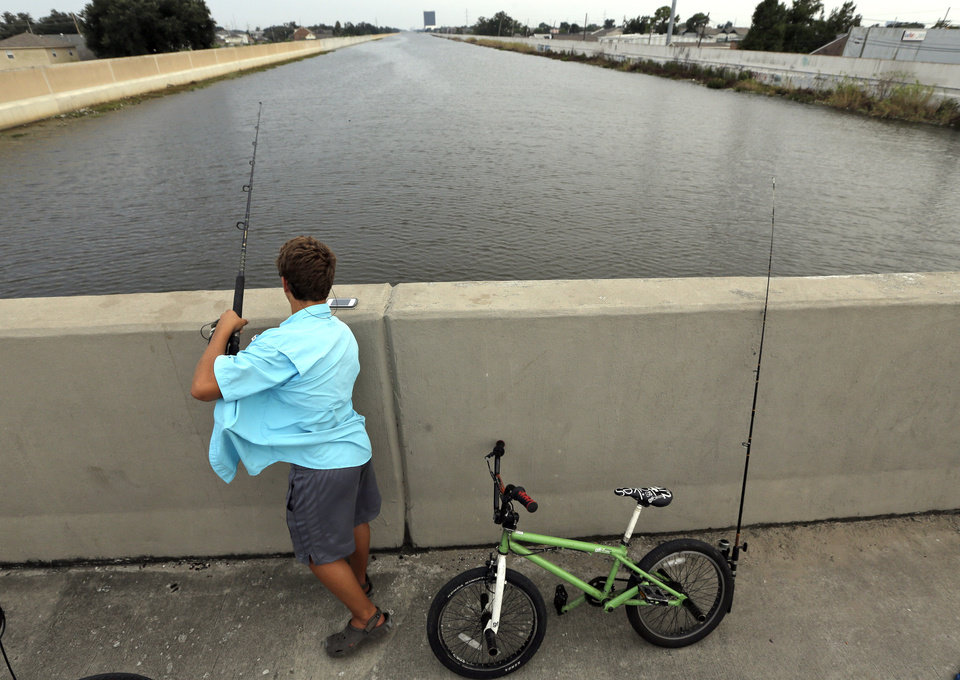 Photo -   Dylan Lacoste, 14, fishes from the 17th Street Canal bridge Monday, Aug. 27, 2012, in New Orleans. Seven years ago this week Hurricane Katrina hit New Orleans. Tropical Storm Isaac is churning it's way across the Gulf of Mexico and could make landfall near New Orleans later this week. (AP Photo/David J. Phillip)