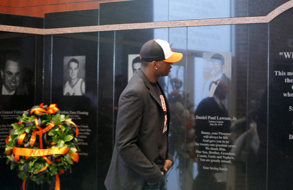 Photo - Desmond Mason visits a memorial honoring the 10 men killed in the 2001 plane crash before the basketball game between Oklahoma State and Texas, Wednesday, Jan. 26, 2011, at Gallagher-Iba Arena in Stillwater, Okla. Photo by Sarah Phipps, The Oklahoman