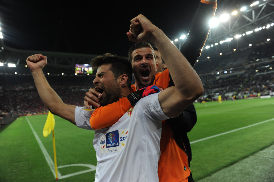 Photo - Sevilla's Coke, left, celebrates with teammate Javi Varas after winning the Europa League soccer final between Sevilla and Benfica, at the Turin Juventus stadium in Turin, Italy, Wednesday, May 14, 2014.  Sevilla beat Benfica 4-2 on penalties to win the Europa League final. (AP Photo/Massimo Pinca)