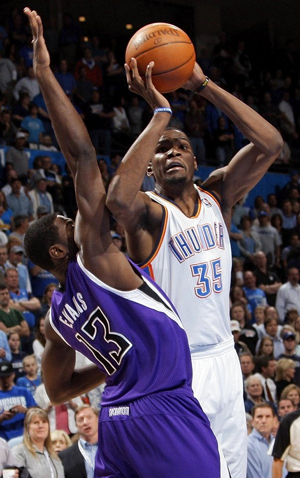 Oklahoma City's Kevin Durant (35) shoots around the defense of Sacramento's Tyreke Evans (13) during the NBA basketball game between the Oklahoma City Thunder and the Sacramento Kings at Chesapeake Energy Arena in Oklahoma City, Friday, April 13, 2012. Photo by Nate Billings, The Oklahoman