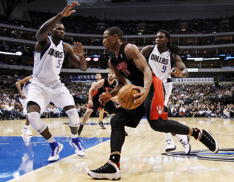 Toronto Raptors' DeMar DeRozan (10) drives to the basket as Dallas Mavericks' Bernard James (5) and Jae Crowder (9) defend in the first half of an NBA basketball game, Wednesday, Nov. 7, 2012, in Dallas. (AP Photo/Tony Gutierrez)