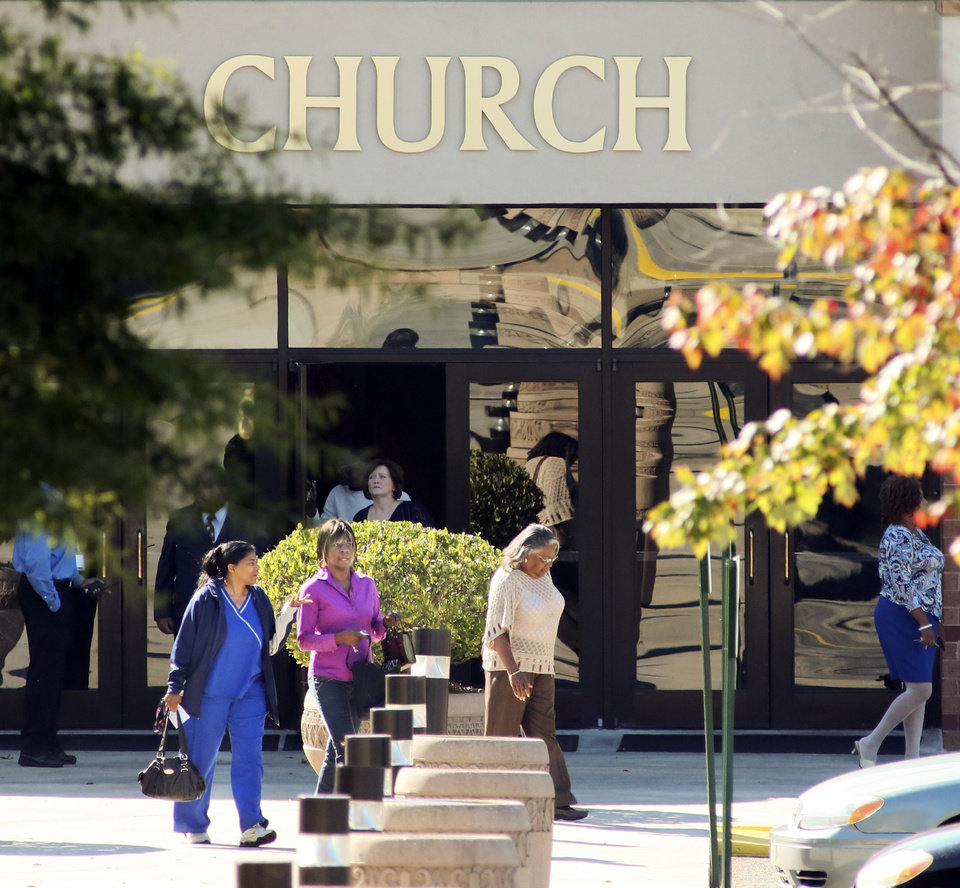 Photo -   Church members leave the main sanctuary building at World Changers Church International in College Park, Ga. on Wednesday, Oct. 24, 2012, next door to the chapel where a church volunteer leading prayer was shot and killed. Authorities were searching for former church employee Floyd Palmer, who is suspected in the shooting. (AP Photo/Atlanta Journal-Constitution, John Spink) MARIETTA DAILY OUT; GWINNETT DAILY POST OUT; LOCAL TV OUT; WXIA-TV OUT; WGCL-TV OUT