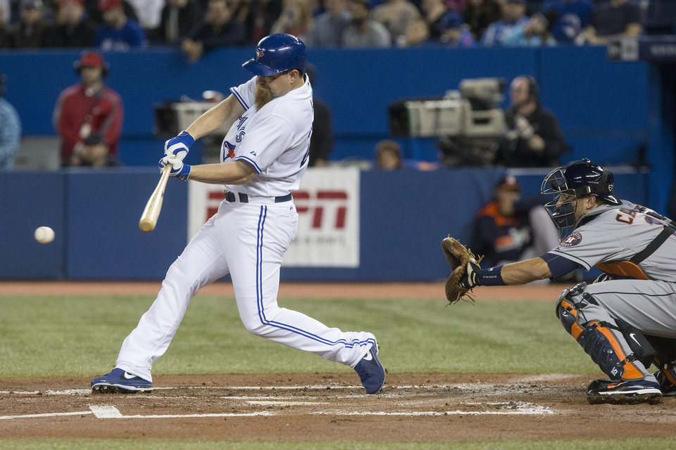 Photo - Toronto Blue Jays' Adam Lind hits a RBI single off Houston Astros starting pitcher Lucas Harrell during the first inning of a baseball game Wednesday, April 9, 2014, in Toronto. (AP Photo/The Canadian Press, Chris Young)