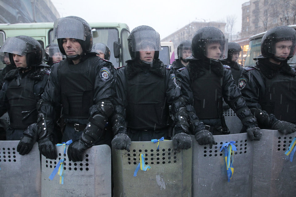 Photo - Ukrainian riot police with ribbons in Ukrainian national colours on their shields block the road next to Pro-European Union activists gathered on the Independence Square in Kiev, Ukraine, Monday, Dec. 9, 2013. Hundreds of police in full riot gear flooded into the center of Kiev on Monday as mass anti-government protests gripped the Ukrainian capital for yet another week, raising fears of an imminent crackdown. (AP Photo/Sergei Chuzavkov)