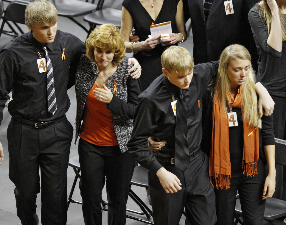 Photo - Alex Budke, left, comforts his mother Shelley as she wipes a tear from her face while with her son Brett and daughter Sara, front, during the memorial service for Oklahoma State head basketball coach Kurt Budke and assistant coach Miranda Serna at Gallagher-Iba Arena on Monday, Nov. 21, 2011 in Stillwater, Okla. The two were killed in a plane crash along with former state senator Olin Branstetter and his wife Paula while on a recruiting trip in central Arkansas last Thursday. Photo by Chris Landsberger, The Oklahoman