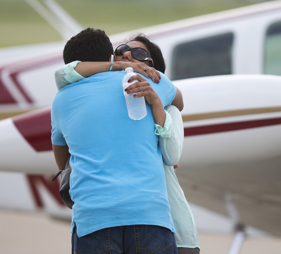 Photo - CORRECTS IDENTIFICATION TO HARIS SULEMAN, NOT BABAR SULEMAN - In this June 19, 2014, photo, Haris Suleman, 17, hugs his mother, Shamim, before he and his father, Babar, took off from Greenwood, Ind., on the first leg of an around-the-world flight. The Indiana teenager who was attempting to set a record for an around-the-world flight was killed when his plane crashed in the Pacific Ocean, and crews were searching Wednesday, July 23, 2014 for his father, who was also onboard. (AP Photo/The Indianapolis Star, Robert Scheer)