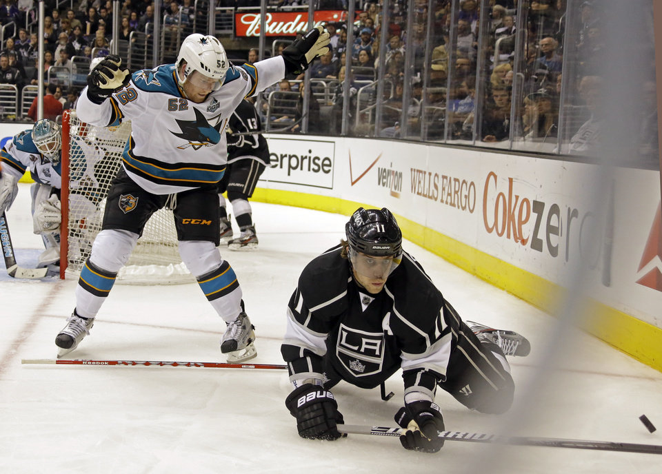Photo - Los Angeles Kings center Anze Kopitar (11), of Yugoslavia, falls and San Jose Sharks defenseman Matt Irwin (52) loses his stick in the second period of an NHL hockey game in Los Angeles Saturday, April 27, 2013. (AP Photo/Reed Saxon)