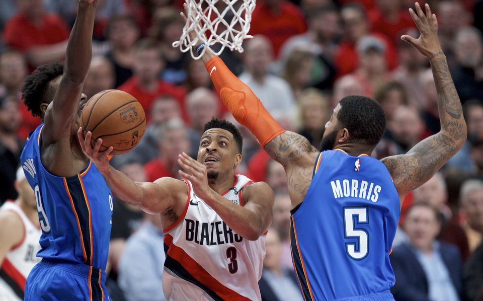 Photo - Portland Trail Blazers guard CJ McCollum, center, shoots between Oklahoma City Thunder forward Jerami Grant, left, and forward Markieff Morris during the second half of Game 2 of an NBA basketball first-round playoff series Tuesday, April 16, 2019, in Portland, Ore. (AP Photo/Craig Mitchelldyer)