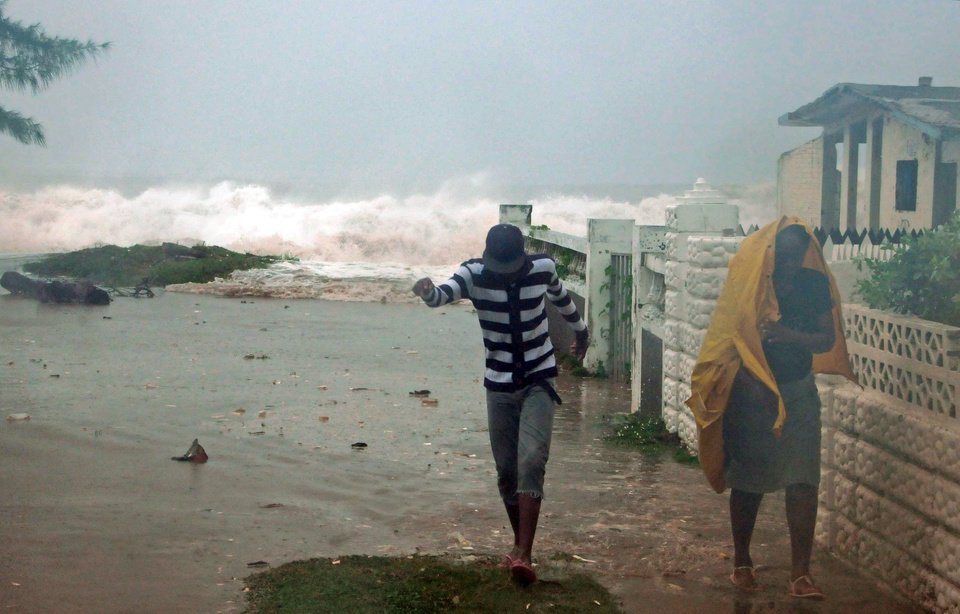 Photo -   Residents evacuate their home as waves crash in the Caribbean Terrace neighborhood of eastern Kingston, Jamaica, Wednesday, Oct. 24, 2012. Hurricane Sandy pounded Jamaica with heavy rain as it headed for landfall near the country's most populous city on a track that would carry it across the Caribbean island to Cuba, and a possible threat to Florida. (AP Photo/Collin Reid)