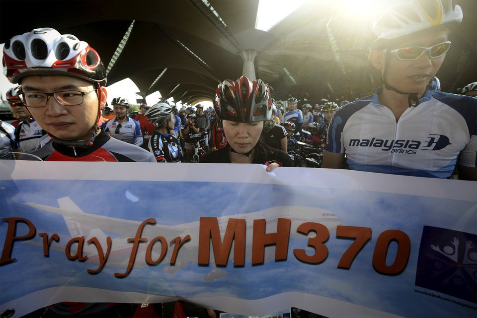 Photo - Cyclists hold a banner as they take a moment of silence and pray during