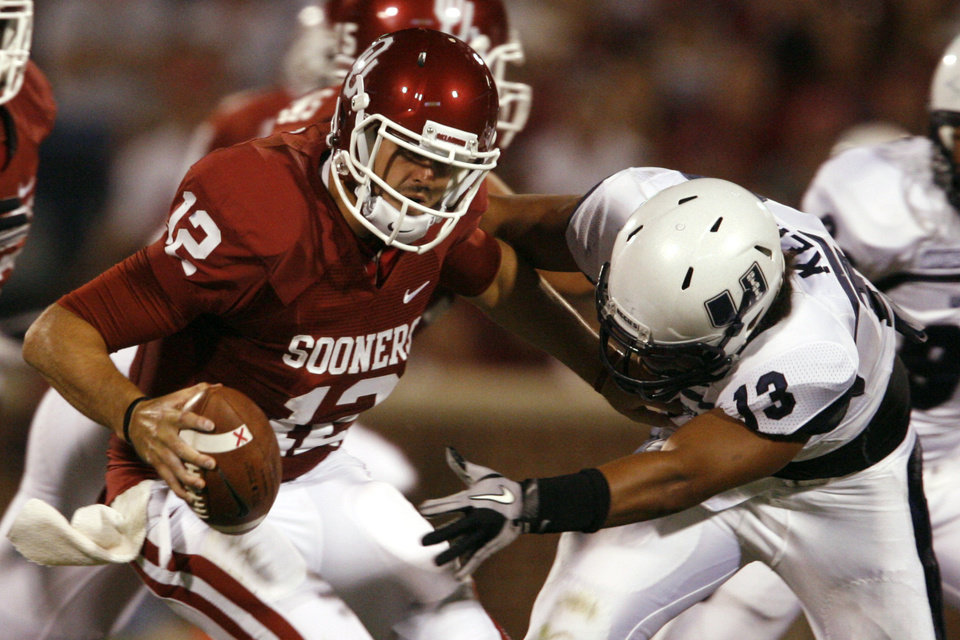 Photo - Quarterback Landry Jones (12) is tackled for a loss by Junior Keiaho (13) during the second half of the college football game between the University of Oklahoma Sooners (OU) and Utah State University Aggies (USU) at the Gaylord Family-Oklahoma Memorial Stadium on Saturday, Sept. 4, 2010, in Norman, Okla.   Photo by Steve Sisney, The Oklahoman