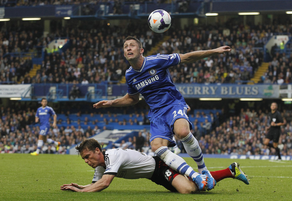 Photo - Chelsea's Gary Cahill, top, attempts to get the ball as Fulham's Scott Parker falls during the English Premier League soccer match between Chelsea and Fulham at Stamford Bridge, London, Saturday, Sept. 21, 2013. (AP Photo/Sang Tan)