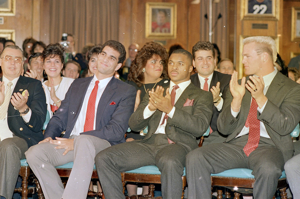 Photo - Heisman trophy hopefuls Paul Palmer, center, Temple running back, and Brian Bosworth, right, Oklahoma linebacker, applaud as it is announced that Vinny Testaverde, left, quarterback from the University of Miami, wins the 1987 Heisman Trophy at the Downtown Athletic Club in New York on Saturday, Dec. 6, 1986. AP ARCHIVE PHOTO