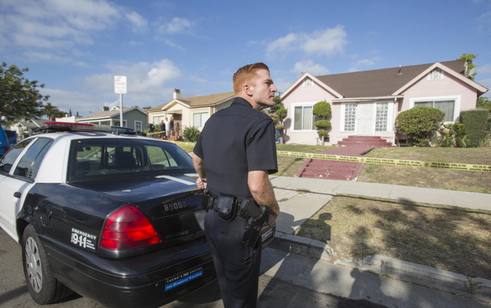 Photo - A police officer stands guard in front of the home of actor Michael Jace on Tuesday, May 20, 2014, in Los Angeles.  Jace, who played a police officer on the hit TV show