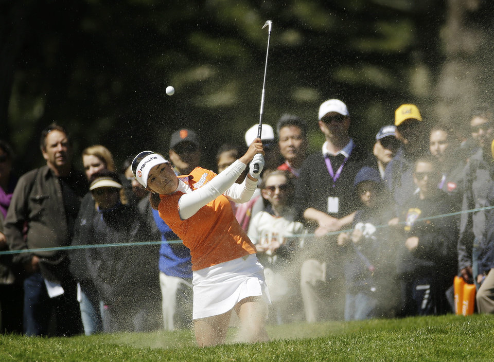Photo - Jenny Shin hits out of a fairway bunker on the sixth hole of Lake Merced Golf Club during the final round of the Swinging Skirts LPGA Classic golf tournament on Sunday, April 27, 2014, in Daly City, Calif. Her shot went straight up and landed back in the bunker. (AP Photo/Eric Risberg)