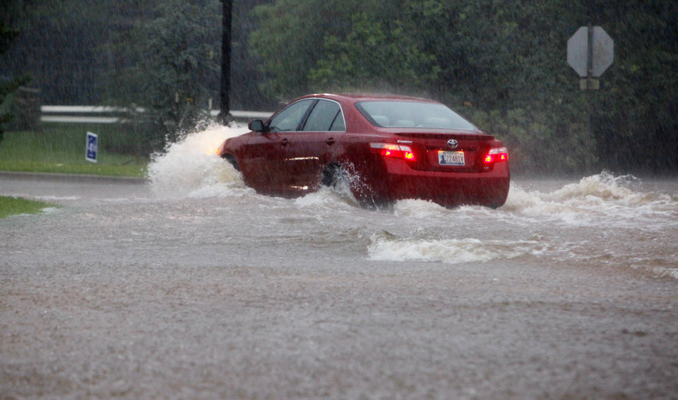 Photo - A car tries to make it through high water on Wilshire Blvd. at Nichols Road during heavy rains in Nichols Hills Monday, June 14, 2010. Photo by Paul B. Southerland, The Oklahoman