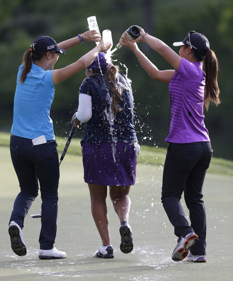 Photo - Lydia Ko, left, and Danielle Kang, right, douse Lizette Salas, with sparkling wine and water as she celebrates winning the Kingsmill Championship golf tournament at the Kingsmill resort  in Williamsburg, Va., Sunday, May 18, 2014.  Salas won her first LPGA event after shooting an even par-71 leaving her at 13-under for the tournament.  (AP Photo/Steve Helber)
