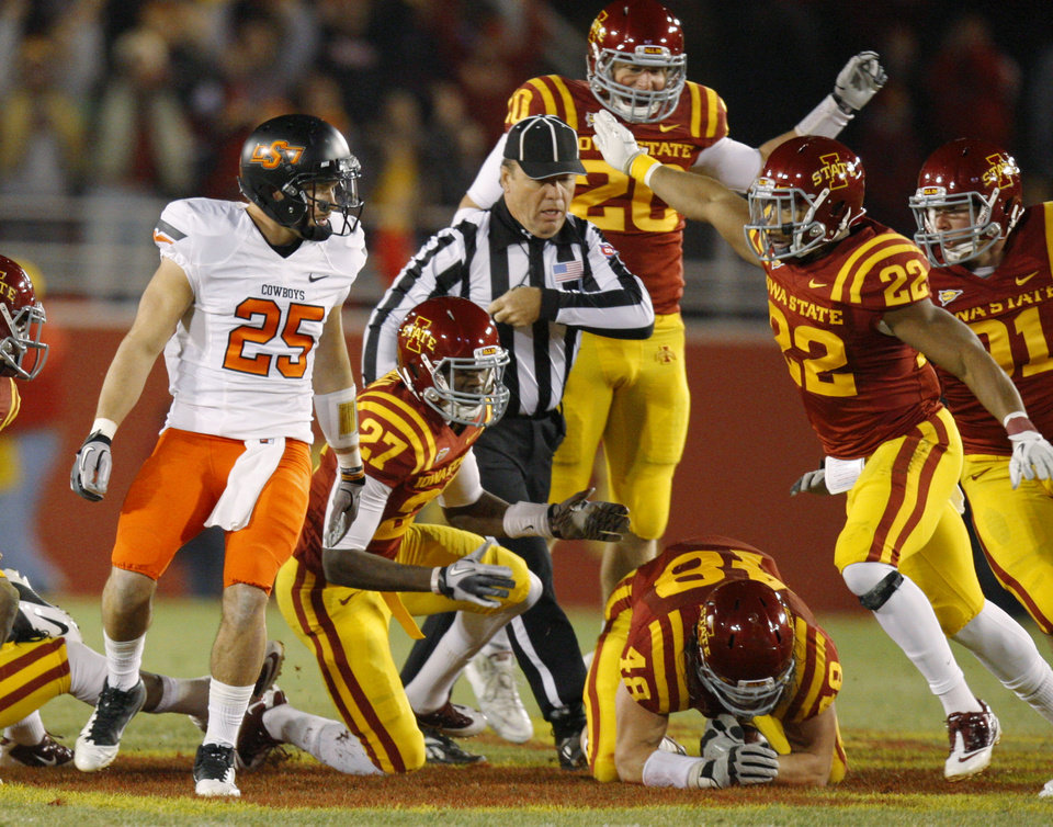 Photo - Oklahoma State's Josh Cooper (25) watches as Iowa State celebrates after a fumble recovery during a college football game between the Oklahoma State University Cowboys (OSU) and the Iowa State University Cyclones (ISU) at Jack Trice Stadium in Ames, Iowa, Friday, Nov. 18, 2011. Photo by Bryan Terry, The Oklahoman