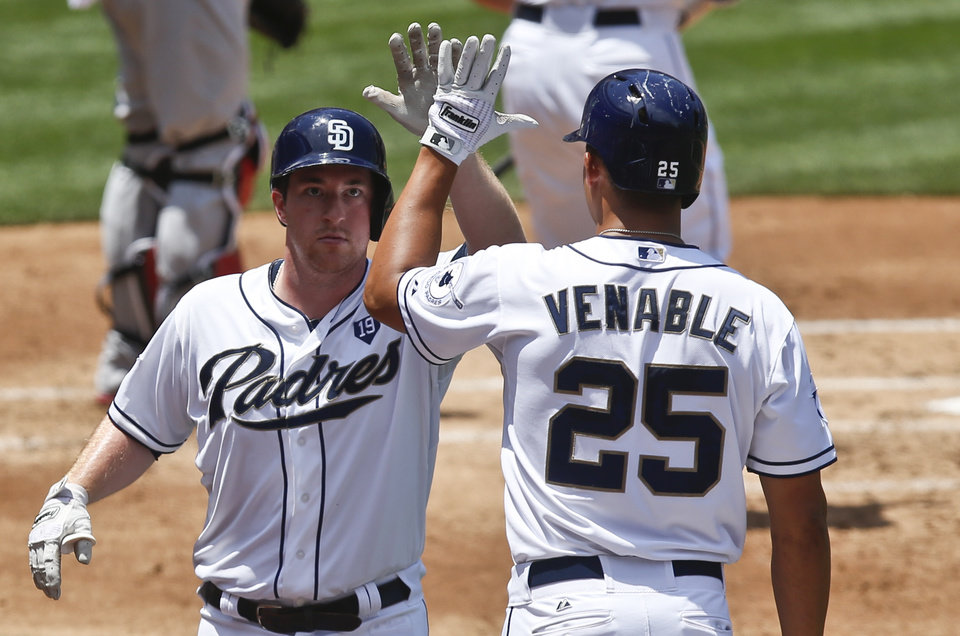 Photo - San Diego Padres' Jedd Gyorko high fives with Will Venable after his solo homer against the St. Louis Cardinals in the second inning of a baseball game Thursday, July 31, 2014, in San Diego.  (AP Photo/Lenny Ignelzi)