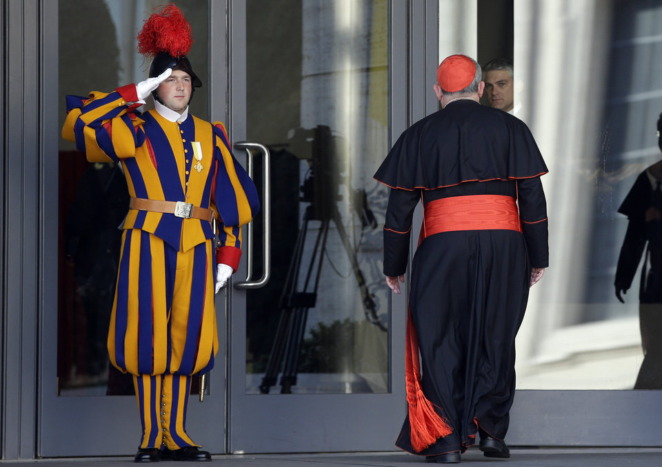 Photo - Vatican Swiss guards salute as a cardinal arrives for a meeting, at the Vatican, Monday, March 4, 2013. Cardinals from around the world have gathered inside the Vatican for their first round of meetings before the conclave to elect the next pope, amid scandals inside and out of the Vatican and the continued reverberations of Benedict XVI's decision to retire. (AP Photo/Andrew Medichini)