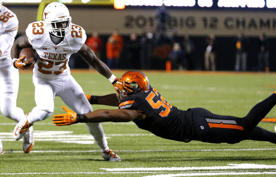 Photo - Texas' Daje Johnson (23) pushes off a tackle attempt by Oklahoma State's Ryan Simmons (52) during the college football game between the Oklahoma State University Cowboys (OSU) the University of Texas Longhorns (UT) at Boone Pickens Staduim in Stillwater, Okla. on Saturday, Nov. 15, 2014.  Photo by Chris Landsberger, The Oklahoman
