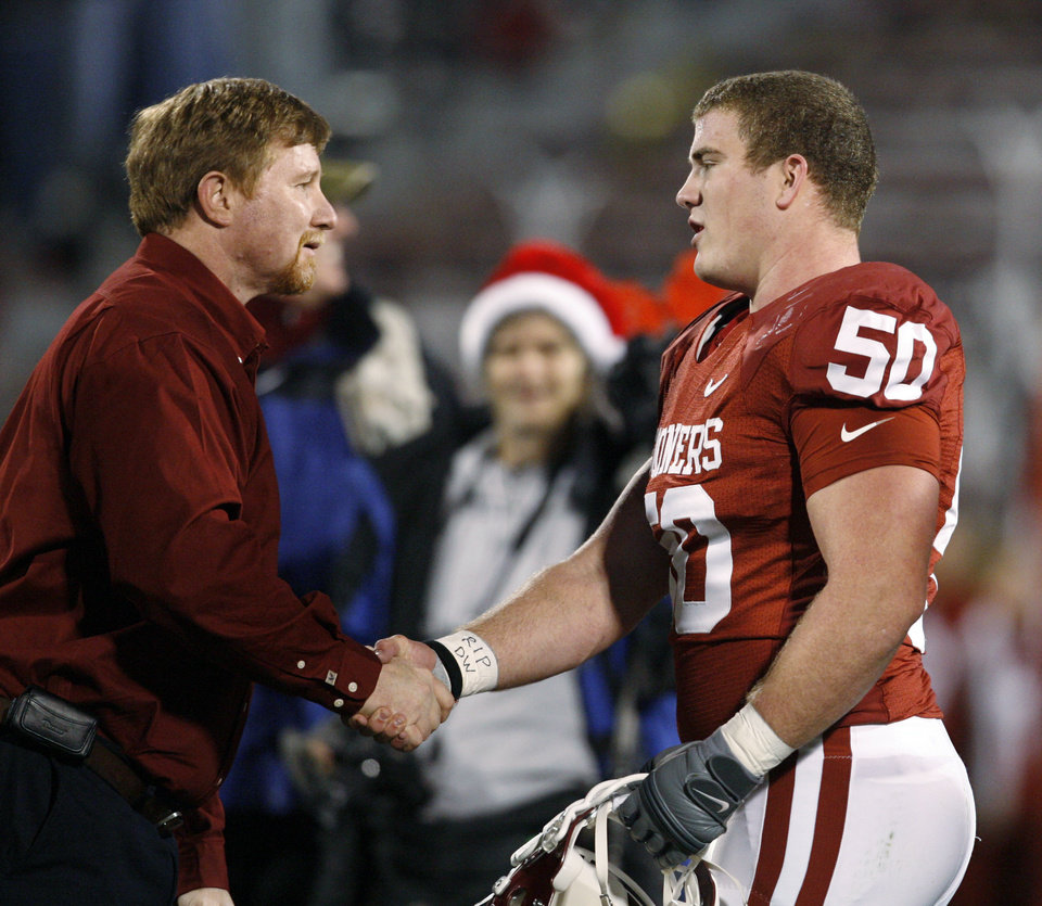 Photo - OU's Jon Cooper shakes hands with Don Key after receiving the Don Key Award before the college football game between the University of Oklahoma Sooners and Texas Tech University at the Gaylord Family -- Oklahoma Memorial Stadium on Saturday, Nov. 22, 2008, in Norman, Okla.   BY STEVE SISNEY, THE OKLAHOMAN