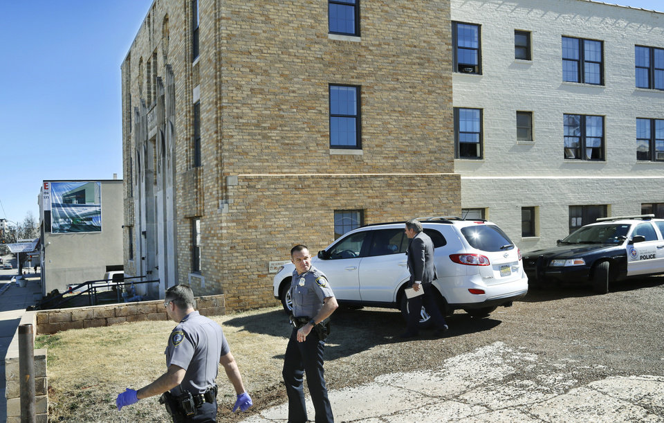 Photo - Uniformed officers and homicide investigators prepare to enter the Rockwall Apartments east of N. Walker on NW 6 Street on Wednesday, Feb. 15, 2017, after the building manager discovered two bodies in one of the rooms. Photo by Jim Beckel, The Oklahoman