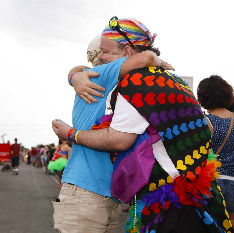 Photo - Sara Cunningham, left, a member of the Mama Bears group in the parade, hugs Frank Baranowski at the OKC Pride Parade on NW 39 in Oklahoma City, Sunday, June 26, 2016. Photo by Kurt Steiss, The Oklahoman