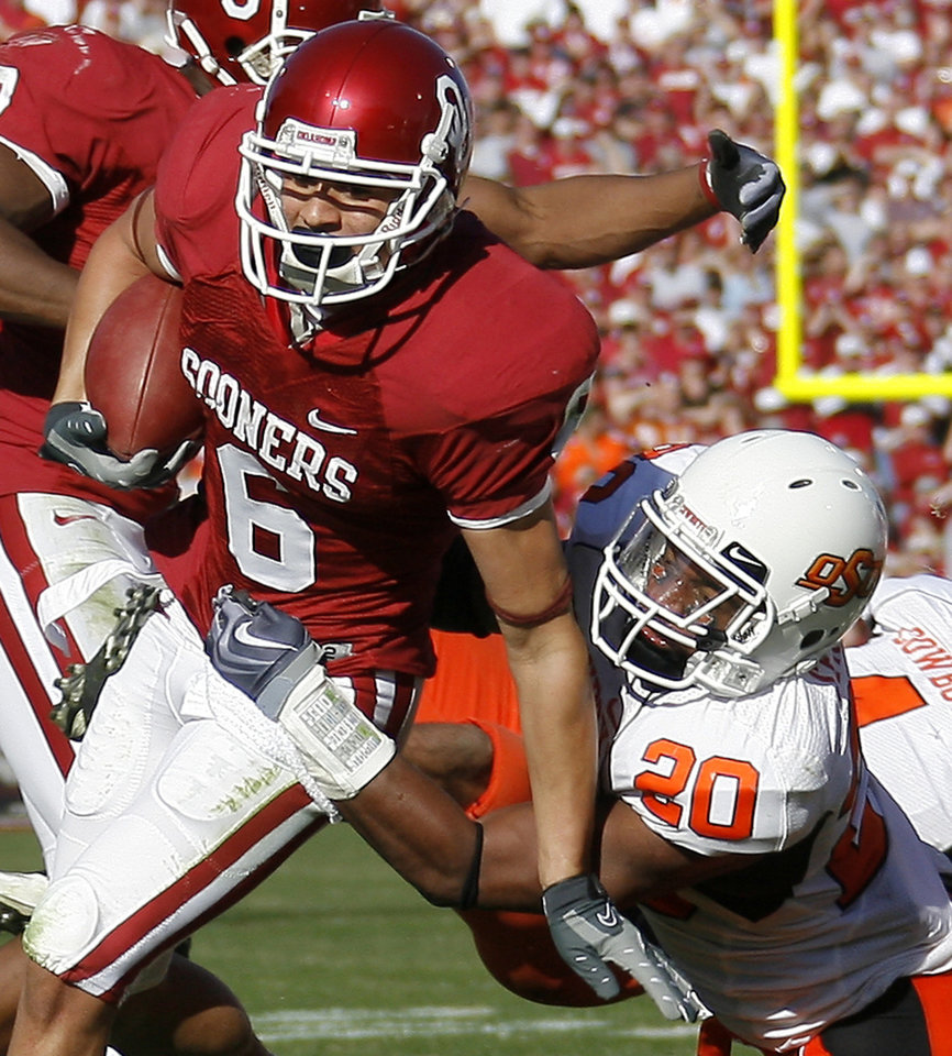 Photo - OU's Cameron Kenney fights of OSU's Andre Sexton during the second half of the Bedlam college football game between the University of Oklahoma Sooners (OU) and the Oklahoma State University Cowboys (OSU) at the Gaylord Family-Oklahoma Memorial Stadium on Saturday, Nov. 28, 2009, in Norman, Okla.