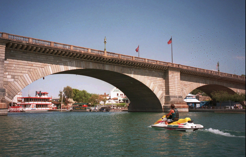 Photo - File-This 1997 file photo shows a lone watercraft rider looking under the  London Bridge, which spans the Colorado River at Lake Havasu City, Ariz. The London Bridge is not falling down, despite a British tabloid saying that the Lake Havasu City tourist attraction could be bulldozed to make way for drug tourism. Lake Havasu City officials heard about the story in The Sun after a local resident visiting the United Kingdom brought back a copy of the tabloid. They say it was a slap in the face and demanded a retraction and an apology. (AP Photo/Arizona Republic, Thomas Ropp,File)     MARICOPA COUNTY OUT; MAGS OUT; NO SALES