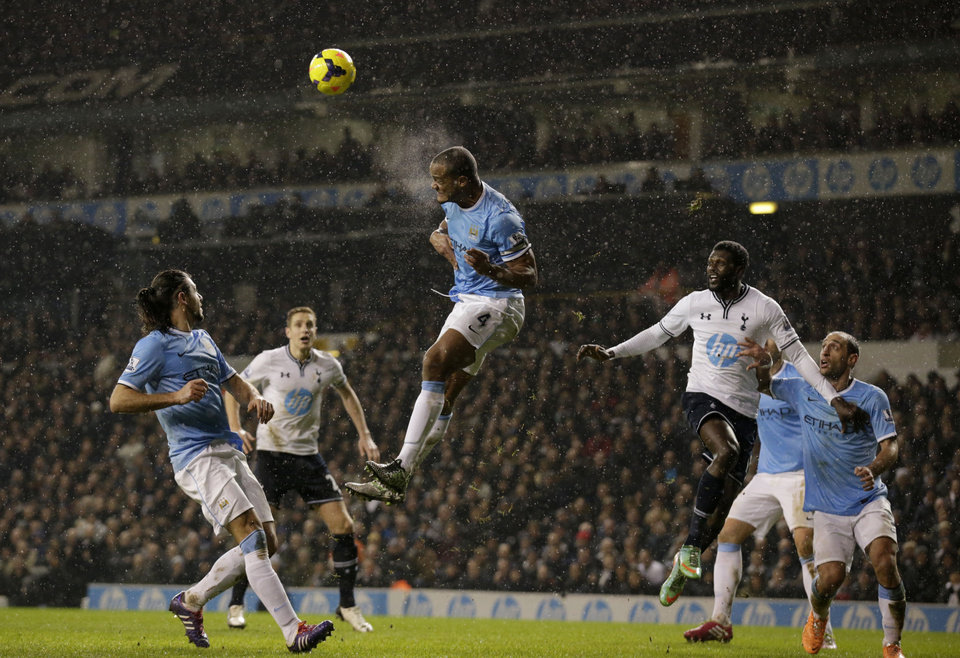 Photo - Manchester City's Vincent Kompany, center, clears the ball away during the English Premier League soccer match between Tottenham Hotspur and Manchester City at White Hart Lane stadium in London, Wednesday, Jan. 29, 2014.  (AP Photo/Matt Dunham)