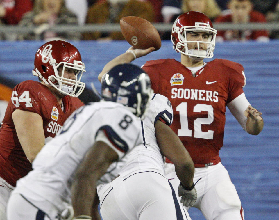 Photo - Oklahoma's Landry Jones (12) throws a pass during the Fiesta Bowl college football game between the University of Oklahoma Sooners and the University of Connecticut Huskies in Glendale, Ariz., at the University of Phoenix Stadium on Saturday, Jan. 1, 2011.  Photo by Bryan Terry, The Oklahoman