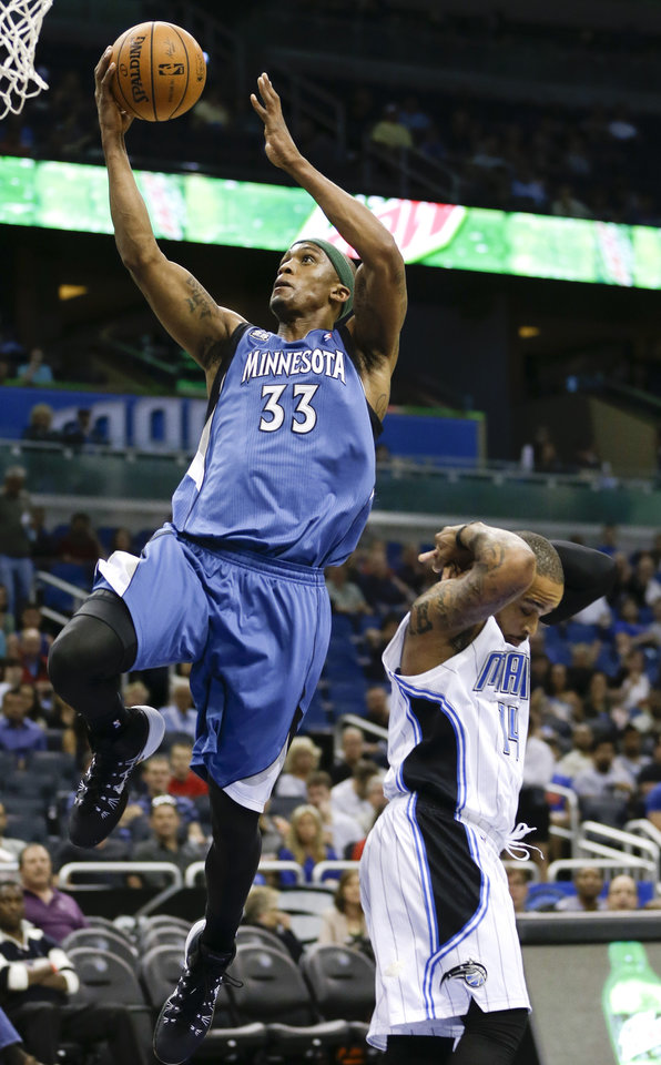 Minnesota Timberwolves' Dante Cunningham (33) gets past Orlando Magic's Jameer Nelson for a basket during the first half of an NBA basketball game in Orlando, Fla., Saturday, April 5, 2014. (AP Photo/John Raoux)