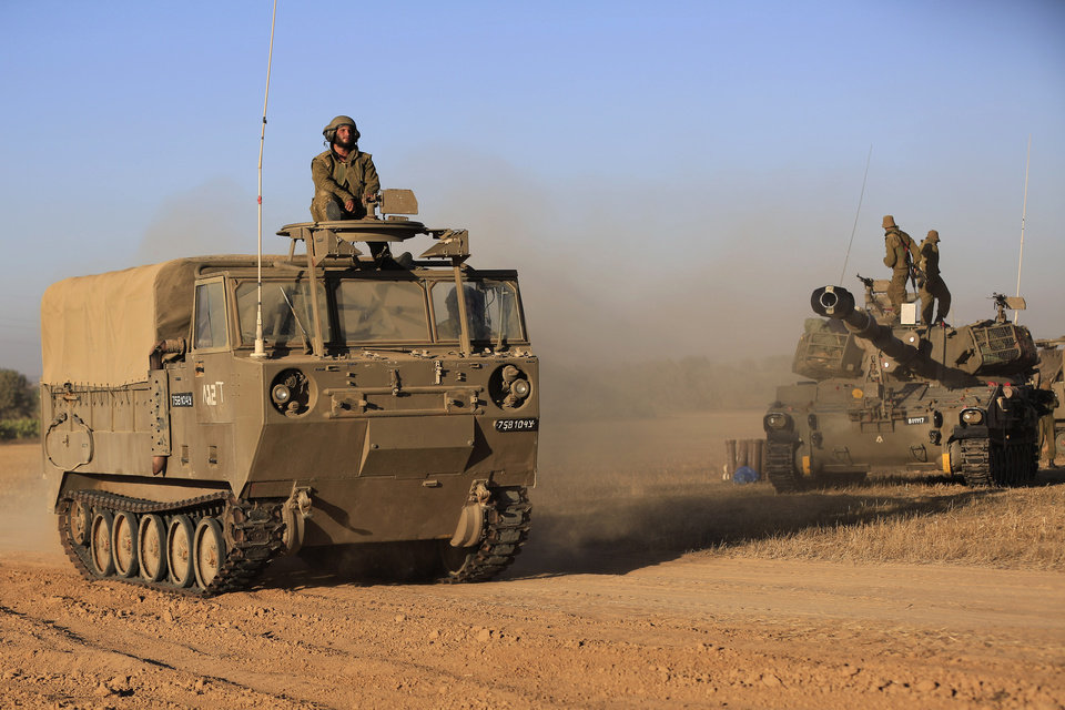Photo - Israeli soldiers on a vehicle, left, drive past a mobile artillery unit, right, at a position on the Israel-Gaza border, Friday, July 11, 2014. Gaza rocket fire struck a gas station and set it ablaze Friday in southern Israel, seriously wounding one person as rocket fire also came from Lebanon for the first time in the four-day-long offensive. Rocket fire by Palestinian militants continued from Gaza toward various locations in southern Israel. (AP Photo/Tsafrir Abayov)