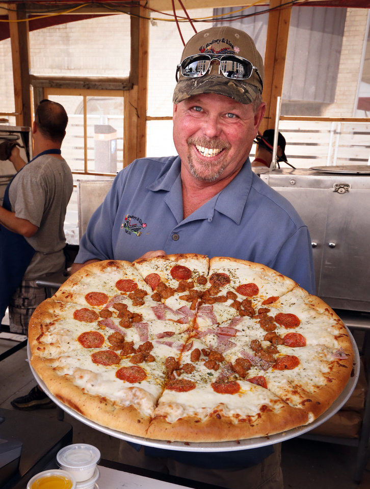 Photo -  Rodney Albers of Rodney and Lisa Ltd. shows a Double Stuff Pizza offered at the Festival of the Arts at OKC's Bicentennial Park on Tuesday in Oklahoma City. [Photo by Steve Sisney, The Oklahoman]