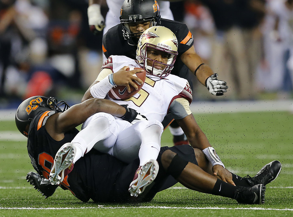 Photo - Florida State's Jameis Winston (5) is sacked by Oklahoma State's Ofa Hautau (98) during the college football game between Oklahoma State University (OSU) and Florida State University (FSU) at the AdvoCare Cowboys Classic at AT&T Stadium in Arlington, Texas on Saturday, Aug. 30, 2014. Photo by Chris Landsberger, The Oklahoman