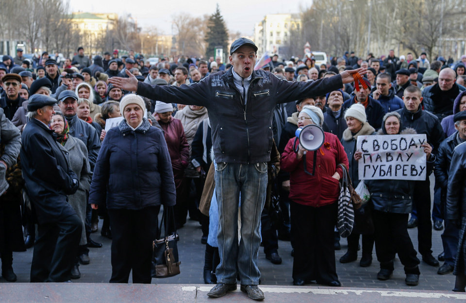 Photo - A man gestures during a pro Russia rally in Donetsk, Ukraine, Tuesday, March 11, 2014. Ukraine's acting president on Tuesday called for the formation of a national guard and for the mobilization of reserves and volunteers into the country's armed forces. The banner at right reads,