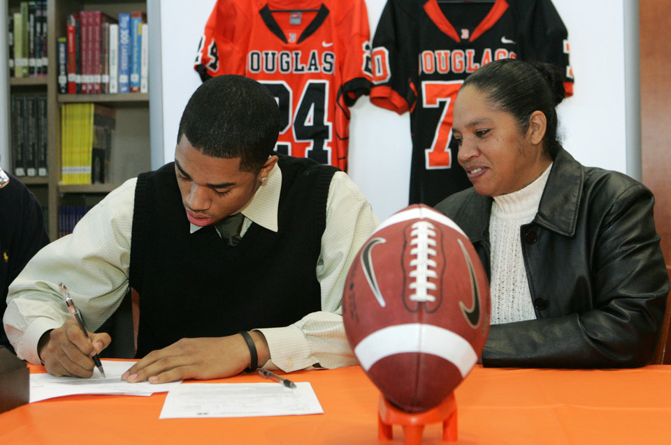Photo - Douglass High School's Destin Stewart signs with the University of Hawaii as his mother Sabena Watts looks on in Oklahoma City, Oklahoma February 4, 2009.  BY STEVE GOOCH, THE  OKLAHOMAN.  ORG XMIT: KOD