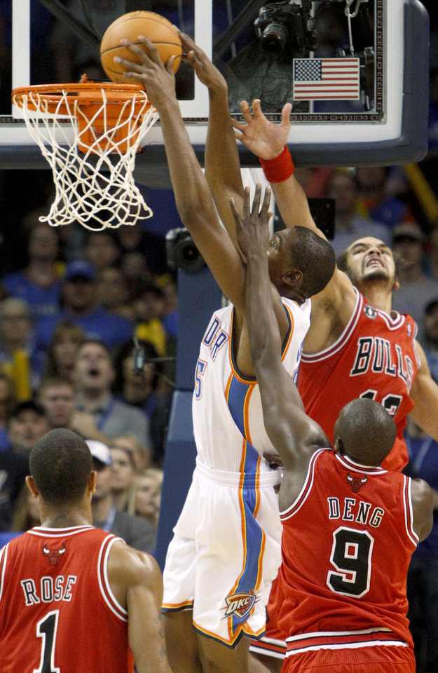 Photo - Oklahoma City's Kevin Durant dunks the ball past Chicago's Joakim Noah, top, and Luol Deng during the NBA basketball game between the Oklahoma City Thunder and the Chicago Bulls in the Oklahoma City Arena on Wednesday, Oct. 27, 2010. Photo by Bryan Terry, The Oklahoman