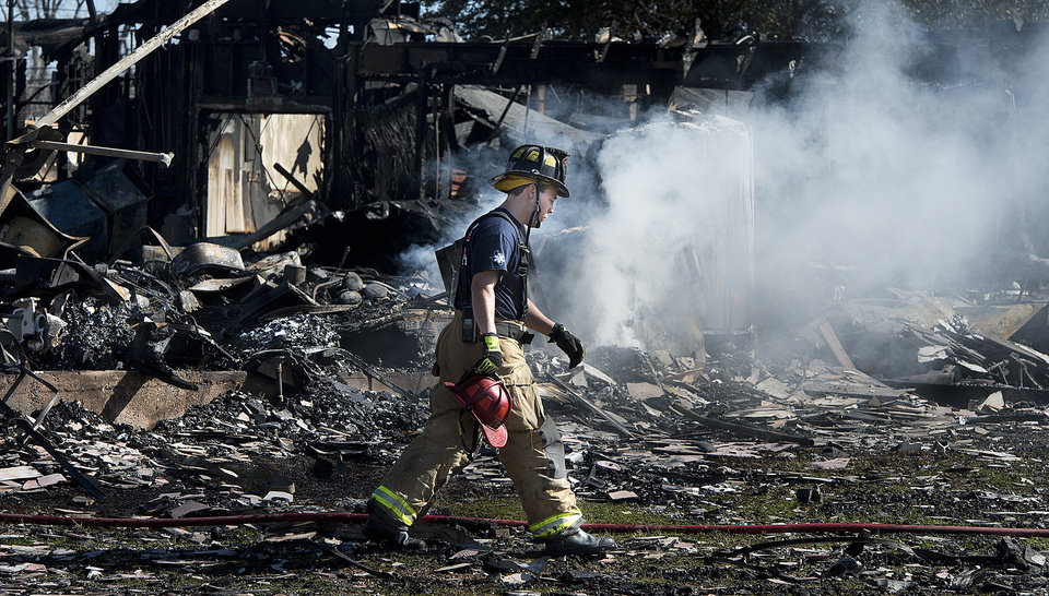A Bryan firefighter walks across the smoking rubble of a Knights of Columbus Hall in Bryan, Texas, Saturday, Feb. 16, 2013. Two Texas fire lieutenants have died of burns after battling a lodge hall fire, and two are hospitalized, a city official said Saturday. (AP Photo/Bryan College Station Eagle, Stuart Villanueva)