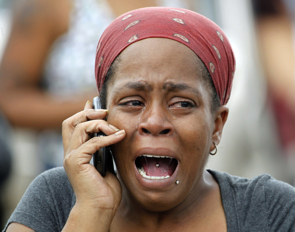 Photo - Nicole Webb cries as she talks on a phone in the parking lot of a store while waiting for her 9-year-old son, a student at Ronald E. McNair Discovery Learning Academy in Decatur, Ga., on Tuesday, Aug. 20, 2013. Superintendent Michael Thurmond says all students at the school east of Atlanta are accounted for and safe and that he is not aware of any injuries. (AP Photo/John Bazemore)