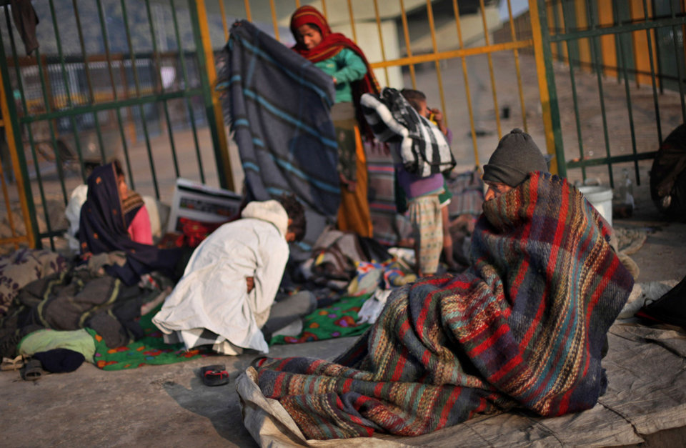 A homeless Indian family rises to start the day, on a pavement on a cold morning in New Delhi, India, Wednesday, Jan. 9, 2013. North India continues to face below average weather conditions with dense fog affecting flights and trains. More than 100 people have died of exposure as northern India deals with historically cold temperatures. (AP Photo/Altaf Qadri)