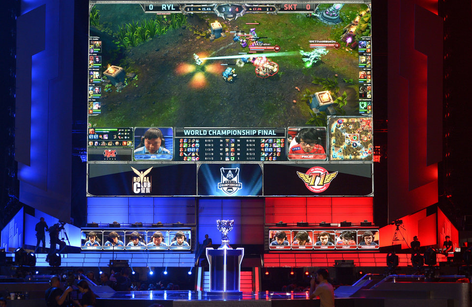 Photo - FILE - In this Oct. 4, 2013, file photo, the teams of China's Royal Club, left, and South Korea's SK Telecom T1 compete at the League of Legends Season 3 World Championship Final in Los Angeles. Robert Morris University Illinois, a small private university in Chicago, is offering hefty scholarships for players of League of Legends, which has become one of the most popular games for organized team competitions. The university said it recognizes the growing legitimacy of what are known as