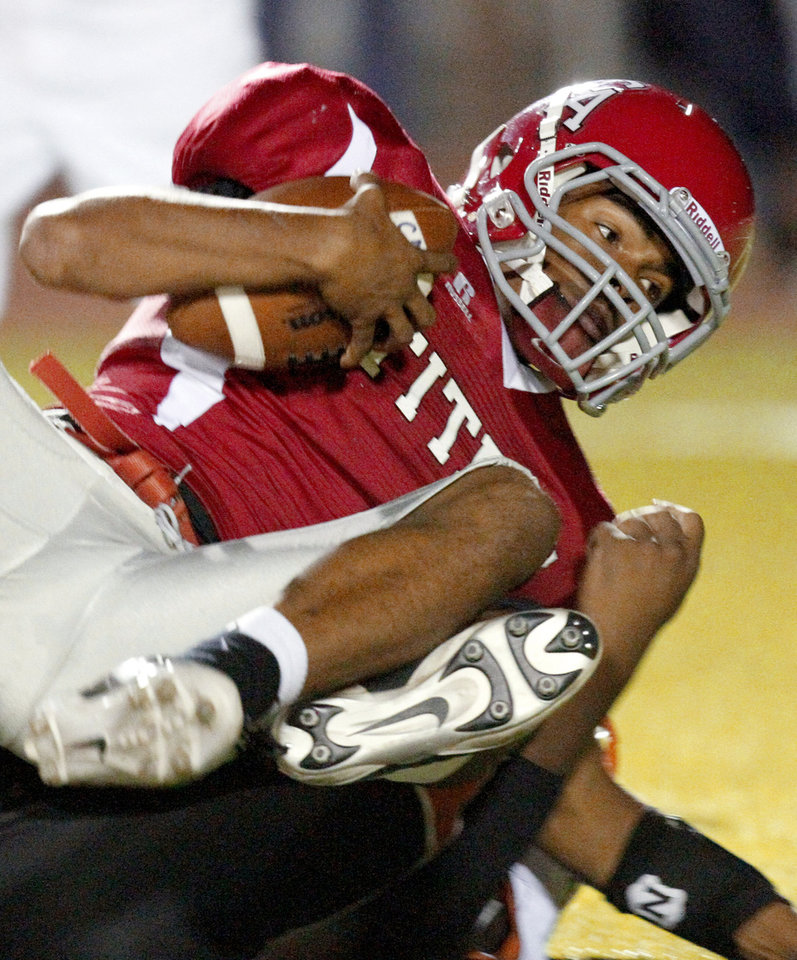Photo - Carl Albert's Dillan Dansby is brought down by Melvin Gilliam of Booker T. Washington during a high school football game in Midwest City, Okla., Friday, September 3, 2010.  Photo by Bryan Terry, The Oklahoman