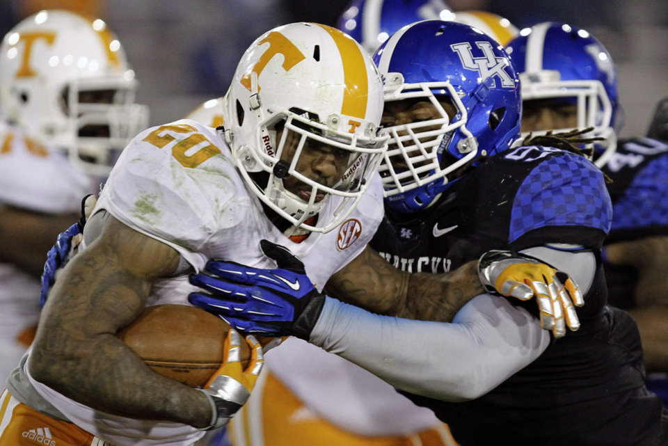 Photo - FILE - In this Nov. 30, 2013, file photo, Kentucky's Za'Darius Smith, right, tries to stop Tennessee running back Rajion Neal (20) on a carry in an NCAA college football game in Lexington, Ky. Smith and Alvin Dupree are back for their senior seasons, good news for Kentucky in many ways. (AP Photo/Garry Jones, File)
