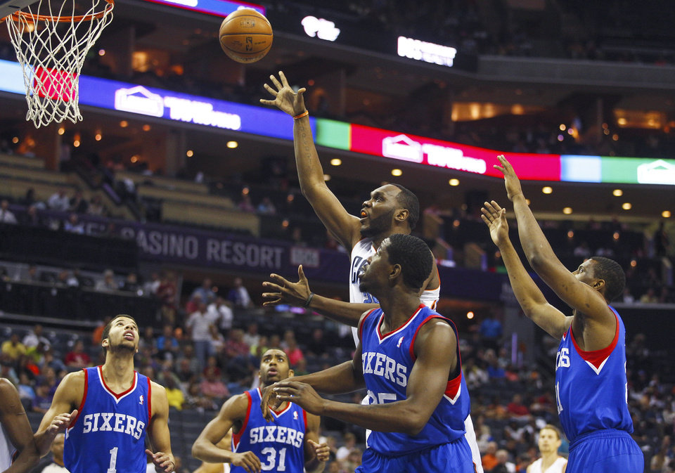 Photo - Charlotte Bobcats center Al Jefferson, center, works to shoot against the Philadelphia 76ers during the first half of an NBA basketball game in Charlotte, N.C., Saturday, April 12, 2014. (AP Photo/Chris Keane)