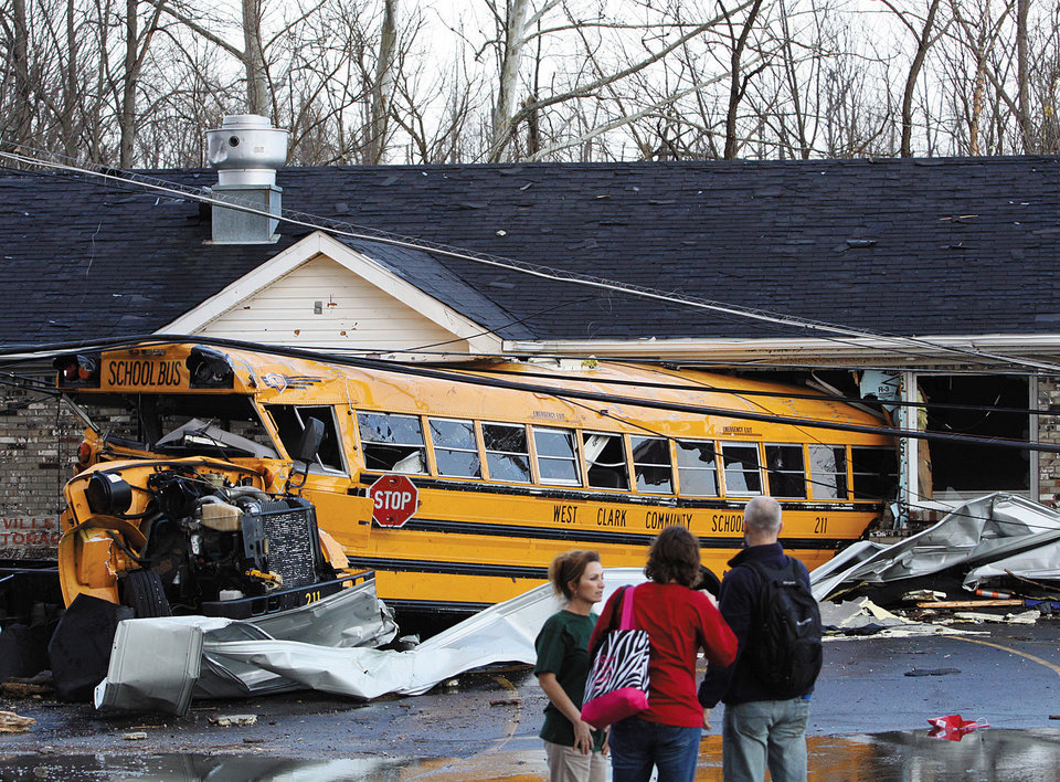 A school bus is crushed into a business on the east side of U.S. 31 in Henryville, Ind., after powerful storms stretching from the U.S. Gulf Coast to the Great Lakes in the north wrecked two small towns and killed at least eight people Friday, March 2, 2012, as the system tore roofs off schools and homes and damaged a maximum security prison. It was the second deadly tornado outbreak this week. (AP Photo/The News and Tribune, C.E. Branham) ORG XMIT: INJEF109